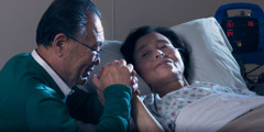 A Christian sister lies in a hospital bed; her husband holds her hand and prays with her