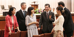 Atsushi and Michiyo Kumagai converse with others at a Kingdom Hall