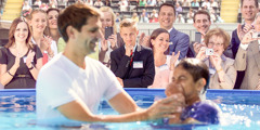 People observe a young person getting baptized, but one young man looks on with uncertainty