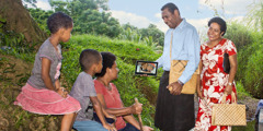 A brother and sister in Fiji use a mobile device to share the good news