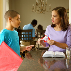 A mother interrupts her personal Bible reading to help her son with his kite