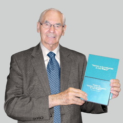 Walter Markin, at the age of 79, holds his pioneer school textbook and sign language DVD