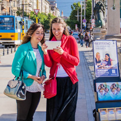 A sister stands beside a public witnessing cart and preaches to a woman