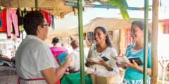 Two sisters share the Bible's message with a merchant in Tipitapa, Nicaragua