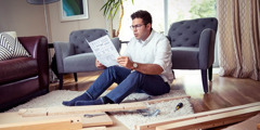 A man reading manufacturer's instructions on assembling a piece of furniture.