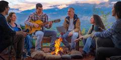 دوستانی با سنهای مختلف دور آتش نشستهاند و یکی از آنها گیتار میزند.