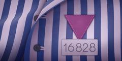 En stripete fangedrakt med en fiolett trekant og et fangenummer, brukt til å identifisere Jehovas vitner i nazistenes konsentrasjonsleirer.