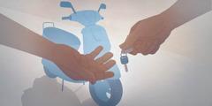 Egy motor tulajdonosa átadja a kulcsot a vásárlónak. A motor a háttérben látható.