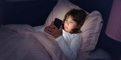 A girl using her smartphone while lying in bed.