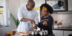 Um casal alegre, a preparar uma refeição.