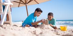 Na plaży dzieci budują zamek z piasku. Ich tata siedzi w pobliżu.