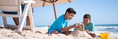 Kinderen maken een zandkasteel aan het strand terwijl hun vader in de buurt zit.
