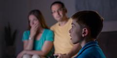 Uma família vendo TV. O pai percebe que as notícias ruins estão afetando seu filho.