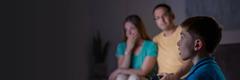 O familie se uită la televizor; tatăl își dă seama că o știre are un puternic impact emoțional asupra băiatului său