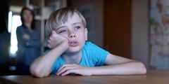 Мама смотрит на сына, который со скучающим видом сидит за столом и смотрит в окно.