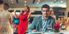 Un hombre, que parece estar molesto, está sentado a la mesa solo mientras su esposa tiene una conversación muy animada con otro matrimonio.
