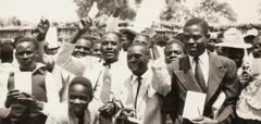 Wasu 'yan'uwa sun daga littafin taimako don iya karatu a yaren Cinyanja a taron da aka yi a birnin Chingola da ke Zambiya, a shekara ta 1954.