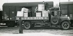 Testigos de Jehová cargando cajas de artículos donados en un vagón de tren para enviarlas a Alemania.
