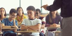 Μαθητής κάθεται στην τάξη ενώ ο καθηγητής του τού κάνει παρατήρηση.