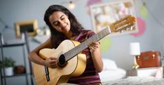 Một bạn nữ chơi ghi-ta trong phòng ngủ.