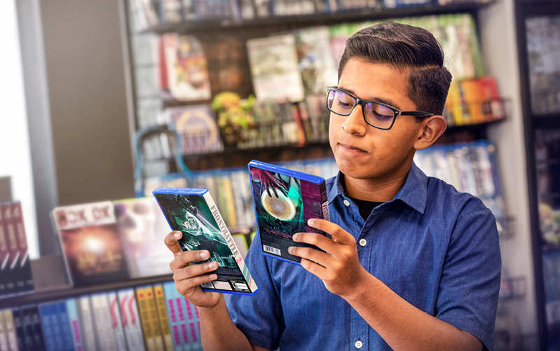 A teenage boy in a video-game store deciding what game he should choose.
