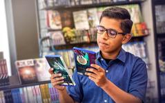 شاب في محل لبيع العاب الفيديو يفكر اي لعبة يختار.