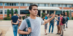 A teenage boy waving his hand in disgust as he walks away from school and a group of students.