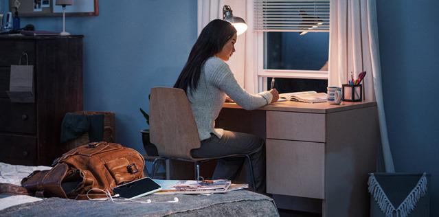 Девушка занимается за письменным столом в своей комнате. Рюкзак, смартфон и журналы лежат у нее за спиной.