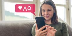 شابة تنظر الى تلفونها وتبتسم، فقد حصلت على ٨٥ اعجابا على صفحتها في مواقع التواصل الاجتماعي