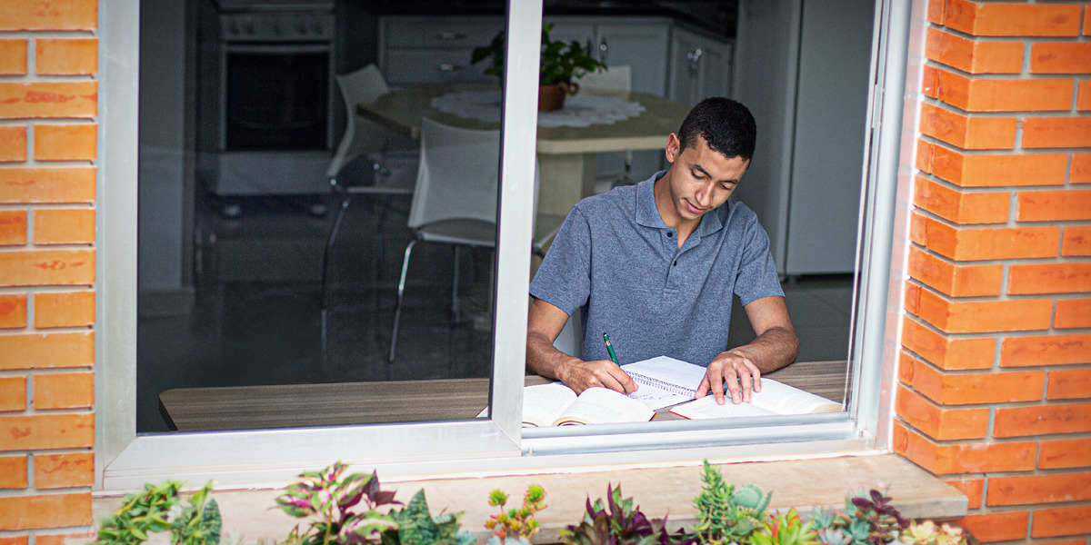Um adolescente estudando em casa numa mesa perto de uma janela.