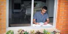 Noormees õpib kodus akna all laua taga.
