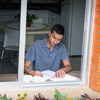 एक नौजवान लड़का अपने घर की खिड़की के पास टेबल-कुर्सी में बैठकर पढ़ाई कर रहा है।