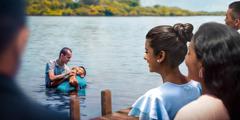 Un home batejant-se en un llac mentres altres el miren.