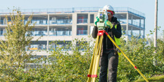 A surveyor inspecting and recording the landscapers' work.