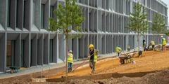 Садовники готовят почву для посевного газона на территории нового британского филиала. Назаднем плане видно, как моют фасадные окна