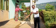 Sébastien și soția lui, Skolastique, făcând curățenie pe lângă casă; el mătură aleea de acces, în timp ce ea curăță balustrada de la intrare