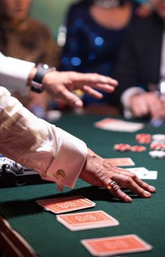 Un bărbat face cărțile la o masă de jocuri din cazinou în timp ce jucătorii îl privesc