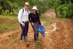Donald și soția lui, Nuria, pe un drum noroios. Ei sunt echipați cu pălării, rucsacuri, umbrele și cizme de cauciuc.