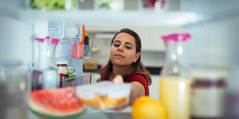 Женщина кладёт контейнер с едой в холодильник.