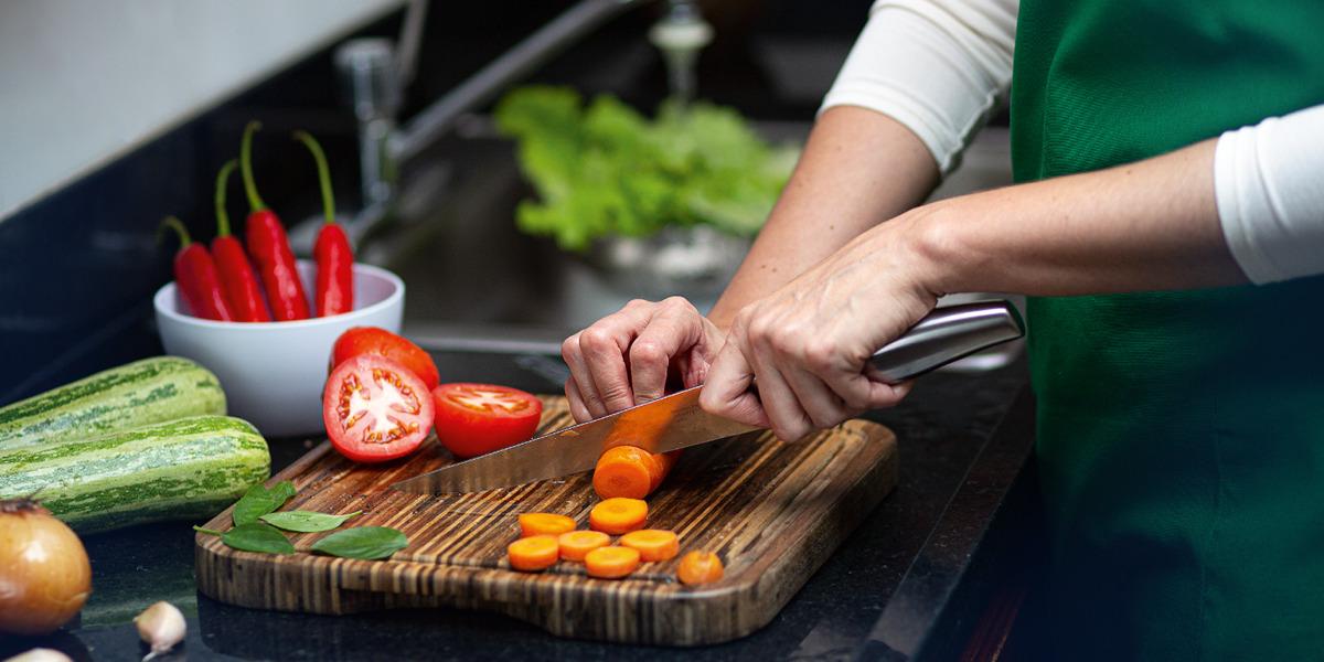 Женщина нарезает овощи на деревянной доске.