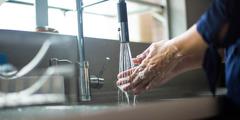 Kobieta myje ręce mydłem iwodą.