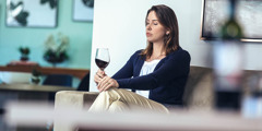A woman staring at her glass of wine while sitting alone at home.