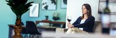 Žena gleda u čašu vina dok sama sedi kod kuće.