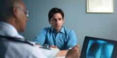 Guardando una radiografia, un medico illustra la diagnosi a un uomo di mezza età che ha un'espressione preoccupata.