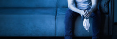 男性がソファに座っている。手には車の鍵とマスクがある。