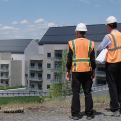 Two workers looking at newly constructed buildings at the World Headquarters of Jehovah's Witnesses.