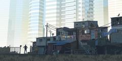 Un hombre en un barrio pobre mirando hacia unos rascacielos lujosos.