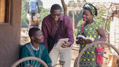 一对耶和华见证人夫妻正在向一名男子传道,给他看圣经影片。