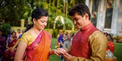 야외에서 결혼식을 올리는 신랑 신부. 신랑이 신부의 손가락에 반지를 끼워 주고 있다.