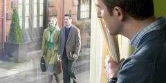 Ein Mann beobachtet Zeugen Jehovas, die gerade von Haus zu Haus unterwegs sind
